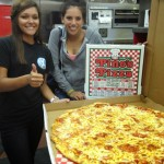 two woman holding an XXL pizza from Pino's Pizza in oc