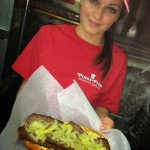Pino's Pizza worker holding cheesesteak with fried onions