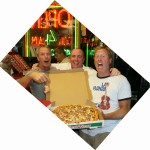 three men holding a sausage Pino's Pizza in ocean city md