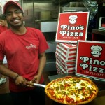 man holding cooked Pino's Pizza in kitchen