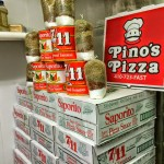 a stack of pizza sauce boxes, canned tomatoes and bagged Pino's Pizza spices