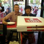 two guys holding two jumbo sized Pino's Pizza boxes in Pino's Pizza of OCMD