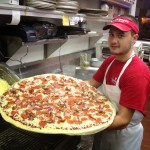 Cook holding XXL pizza with bacon at Pino's Pizza