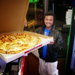 man holding jumbo sized half pepperoni Pino's Pizza in OCMD