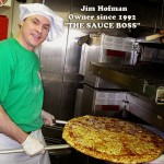 Jim Hofman of Pino's Pizza holding an extra large pizza in oven