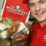 Man holding Pino's Pizza seasoning in bags in jar