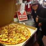 man in black jacket giving thumbs up next to jumbo sized Pino's Pizza