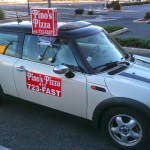 white and black mini cooper with Pino's Pizza delivery signs on it