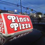 a Pino's Pizza delivery sign for car at night