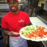 Pino's Pizza employee holding a raw half peppers and pepperoni pizza in kitchen at Pino's Pizza OC